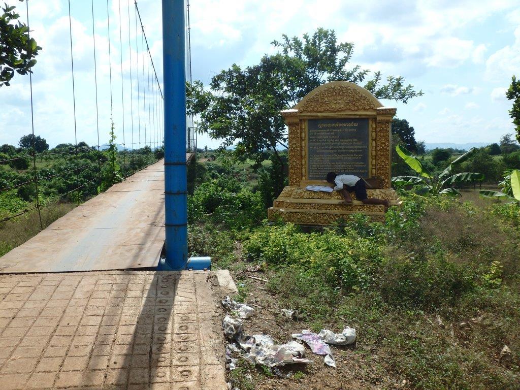 CBPD 吊り橋横に建てられた記念碑上で勉強に励む子供